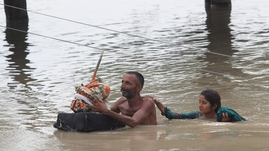 Pakistan villagers wade through floodwaters in Rajanpur, Pakistan, Pakistan, Thursday, July 23, 2015. The country's military has deployed helicopters and boats Wednesday to evacuate flood victims, as 285,000 have been affected by monsoon rains and flash floods in and around the city of Chitral in Pakistan's Khyber Pakhtunkhwa province, according to the National Disaster Management Authority. (AP Photo/Asim Tanveer)