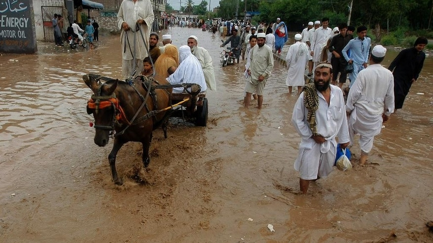 People wade through a flooded street after heavy rains in a suburb of Peshawar, Pakistan, Thursday, July 23, 2015. The country's military has deployed helicopters and boats Wednesday to evacuate flood victims, as 285,000 have been affected by monsoon rains and flash floods in and around the city of Chitral in Pakistan's Khyber Pakhtunkhwa province, according to the National Disaster Management Authority. (AP Photo/Mohammad Sajjad)