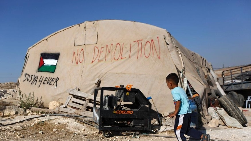 In this Tuesday, July 21, 2015, photo, a Palestinian boy runs outside his family tent in the village of Susiya, south of the West Bank city of Hebron. Residents of this dusty village are bracing for Israeli bulldozers to come and knock down their makeshift homes of tarp, wood and wire any day now. But as they wait for the military order to be carried out, villagers are rallying support from Western governments. (AP Photo/Majdi Mohammed)