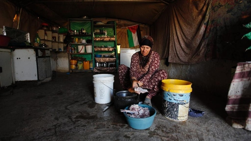 In this Tuesday, July 21, 2015, photo, a Palestinian woman cooks in her family tent in the village of Susiya, south of the West Bank city of Hebron. Residents of this dusty village are bracing for Israeli bulldozers to come and knock down their makeshift homes of tarp, wood and wire any day now.  But as they wait for the military order to be carried out, villagers are rallying support from Western governments. (AP Photo/Majdi Mohammed)