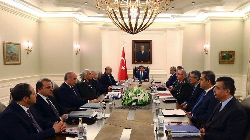 In this Thursday, July 23, 2015 photo, Turkish Prime Minister Ahmet Davutoglu, center, his ministers, military commanders and intelligence officials gather during a security meeting in Ankara, Turkey, hours before Turkish warplanes struck Islamic state group targets across the border in Syria. (Hakan Goktepe/Pool Photo via AP)