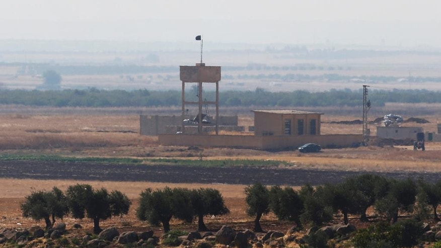 As seen from outskirts of the village of Seve, on the Turkish side of the border, a Syrian opposition group flag flies on a building in the the outskirts of the village of Havar in Syria, Friday, July 24, 2015. Turkish warplanes struck Islamic State group targets across the border in Syria early Friday, government officials said, a day after IS militants fired at a Turkish military outpost, near the area of where the photo was taken, killing a soldier. The bombing is a strong tactical shift for Turkey which had long been reluctant to join the U.S.-led coalition against the extremist group. (AP Photo/Emrah Gurel)