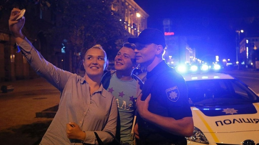 In this photo taken, Wednesday, July 15, 2015, a couple takes a photograph with a Ukrainian police officer in downtown Kiev, Ukraine. Kiev residents approach members of a new police force that has hit the streets, and even ask to take a picture with them. It's being welcomed as the Ukrainian government's first visible reform since it came to power in February 2014. (AP Photo/Sergei Chuzavkov)