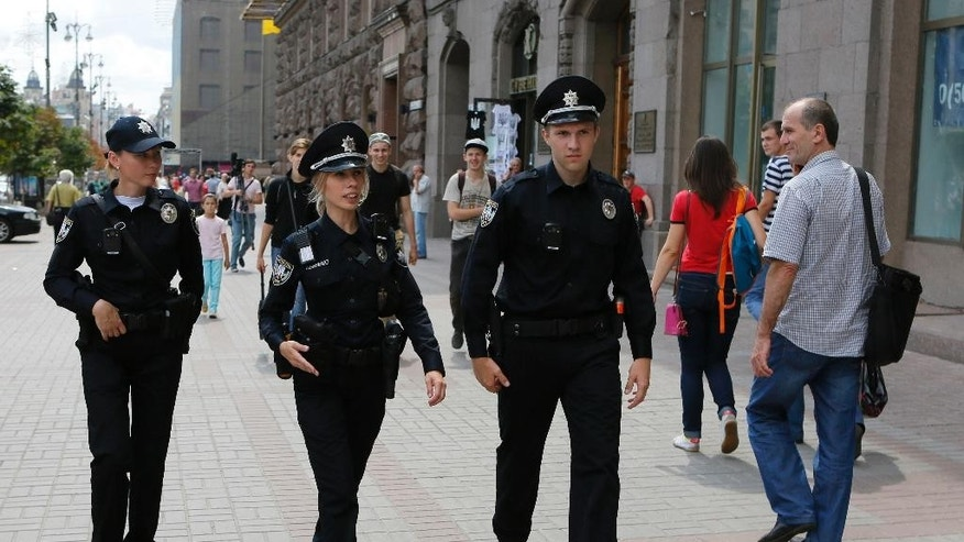 In this photo taken, Tuesday, July 14, 2015, Ukrainian police officers Lesya Kishkel, 32, left, Katerina Lishnevska, 27, and Roman Romanyuk, 23, right, patrol in downtown Kiev, Ukraine. Kiev residents approach members of a new police force that has hit the streets, and even ask to take a picture with them. It's being welcomed as the Ukrainian government's first visible reform since it came to power in February 2014. (AP Photo/Sergei Chuzavkov)