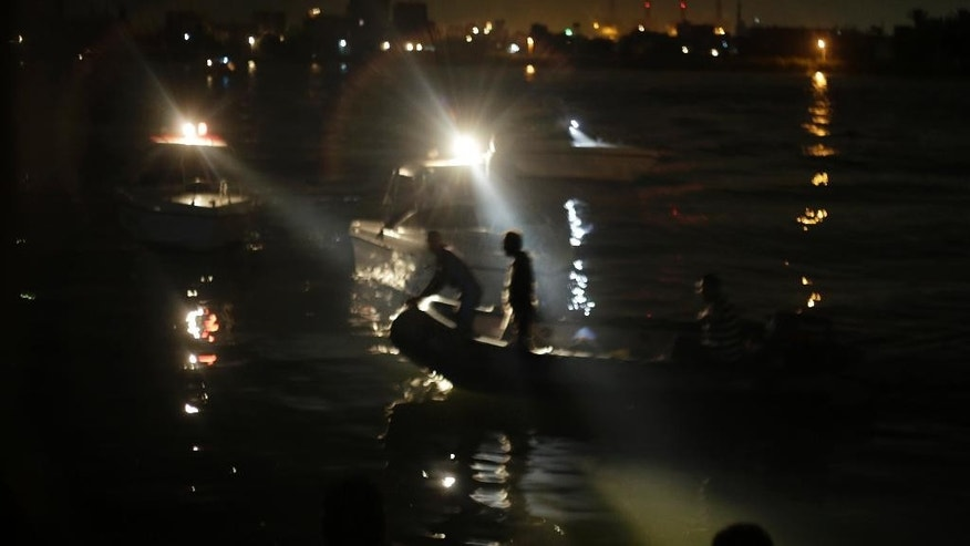 Egyptian rescuers look for victims of a passenger boat after it sank in the river Nile in Giza, south of Cairo, Egypt, Thursday, July 23, 2015. Egypt's Interior ministry says more than a dozen civilians have drowned when the passenger boat traveling down the Nile near Cairo collided with a scow, causing the boat to capsize.  (AP Photo/Amr Nabil)