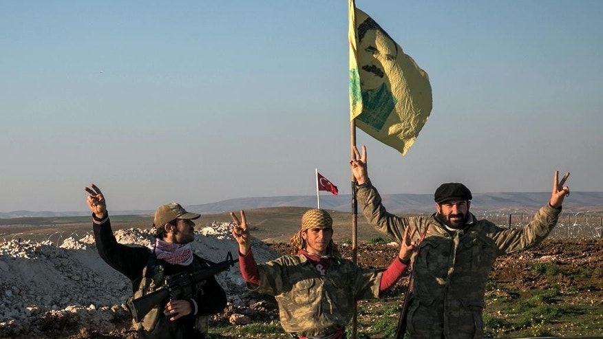 FILE - In this Sunday, Feb. 22, 2015, file photo, Syrian Kurdish militia members of YPG make a V-sign next to poster of Abdullah Ocalan, jailed Kurdish rebel leader, and a Turkish army tank in the background in Esme village in Aleppo province, Syria. Turkish jets struck camps belonging to Kurdish militants in northern Iraq Friday and Saturday in what were the first strikes since a peace deal was announced in 2013. The strikes in Iraq targeted the Kurdistan Workers' Party, or PKK, whose affiliates have been effective in battling the Islamic State group. (AP Photo/Mursel Coban, Depo Photos, File)
