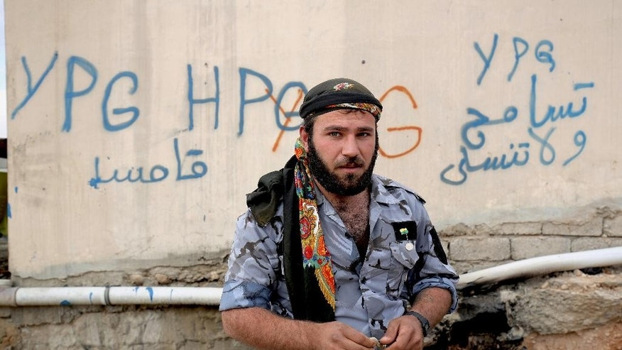 FILE - In this Thursday Jan. 29, 2015 file photo, a Syrian fighter from the Syria-based People's Protection Units better known as the YPG stands in front of a wall covered with graffiti in the town of Sinjar northern Iraq. Turkish jets struck camps belonging to Kurdish militants in northern Iraq Friday and Saturday in what were the first strikes since a peace deal was announced in 2013. The strikes in Iraq targeted the Kurdistan Workers' Party, or PKK, whose affiliates have been effective in battling the Islamic State group. (AP Photo/Bram Janssen, File)