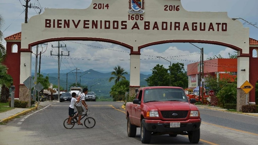 "In this July 20, 2015 photo, a car drives past the entrance to the town of Badiraguato, Mexico. Tucked into the foothills where the coastal stretches of flat corn and tomato fields meet the imposing mountains of the Sierra Madre, Badiraguato, the hometown of drug lord Joaquin ""El Chapo"" Guzman, remains mired in poverty. (AP Photo/Fernando Brito)"