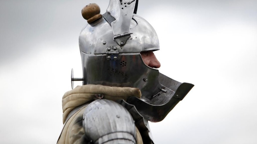 A man wears a armor as he attends a reenactment of the Battle of Agincourt, in Agincourt, northern France, Saturday, July 25, 2015. The French are hosting a reenactment of the clash with England this weekend. More than 800 people in Medieval garb are gathering at the site to commemorate the battle, which was a turning point in the Hundred Years' War. (AP Photo/Thibault Camus)