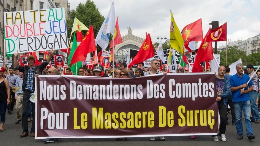 """Kurdish demonstrators protest in Paris, France, Saturday, July 25, 2015, denouncing the deaths of 32 people at a suicide bombing Monday, July 20, in Suruc, southeastern Turkey. Turkish warplanes struck Islamic State group targets across the border in Syria early Friday, in a strong tactical shift for Turkey which had long been reluctant to join the U.S.-led coalition against the extremist group. The banner reads: """"We demand accountability for the massacre of Suruc""""  and """"Stop the double games of Erdogan.""""  (AP Photo/Jacques Brinon)"""