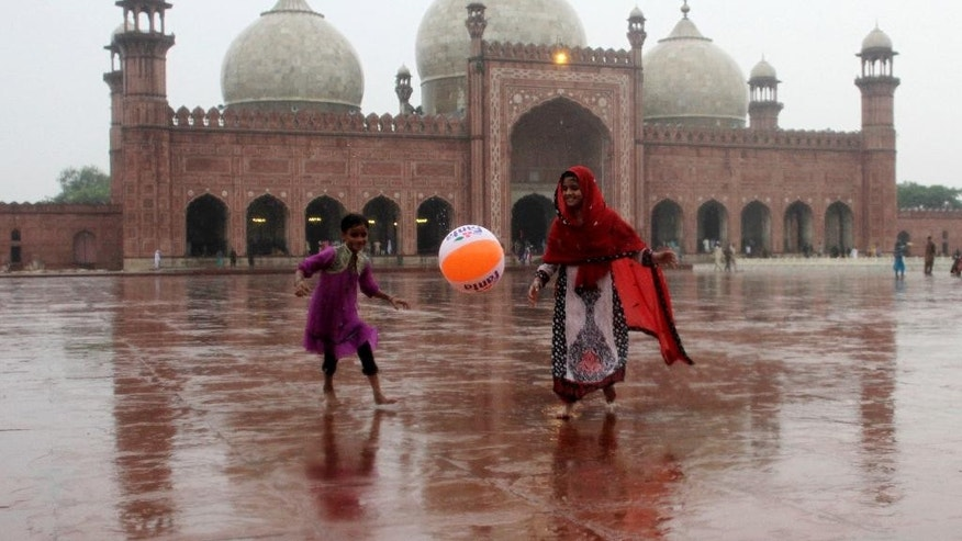 Pakistani children play in the rain outside the historical Badshahi mosque in Lahore, Pakistan, Friday, July 24, 2015.  Pakistani authorities say flash floods, triggered by monsoon rains, have killed 12 more people across the country, bringing the overall death toll since early last week to 15, as rescuers struggle to move those stranded to safer places. (AP Photo/K.M. Chaudary)