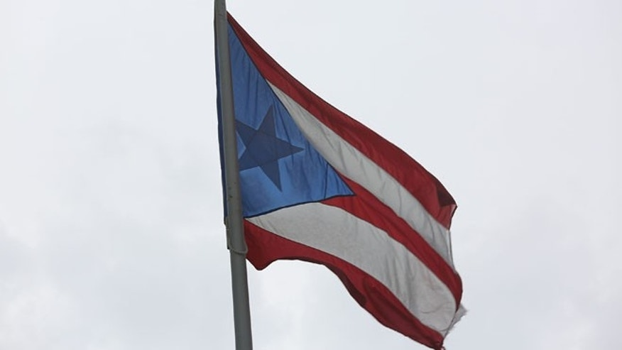 SAN JUAN, PUERTO RICO - JULY 01:  The Puerto Rican flag flies near the Capitol building as the island's residents deal with the government's $72 billion debt on July 1, 2015 in San Juan, Puerto Rico. Governor of Puerto Rico Alejandro García Padilla said in a speech recently that the people of Puerto Rico will have to make sacrifices and share the responsibilities to help pull the island out of debt. (Photo by Joe Raedle/Getty Images)