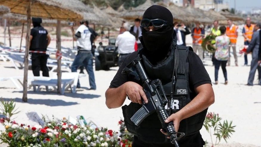 FILE - In this Monday, June 29, 2015 file photo, a hooded Tunisian police officer stands guard ahead of the visit of top security officials of Britain, France, Germany and Belgium at the scene of Friday's shooting attack in front of the Imperial Marhaba hotel in the Mediterranean resort of Sousse, Tunisa. Tunisia's parliament on Friday, July 24 voted overwhelmingly to pass the country's new anti-terror law after a pair of devastating attacks against tourists, but critics fear the new legislation may endanger this North African nation's hard won freedoms.  (AP Photo/Abdeljalil Bounhar, file)