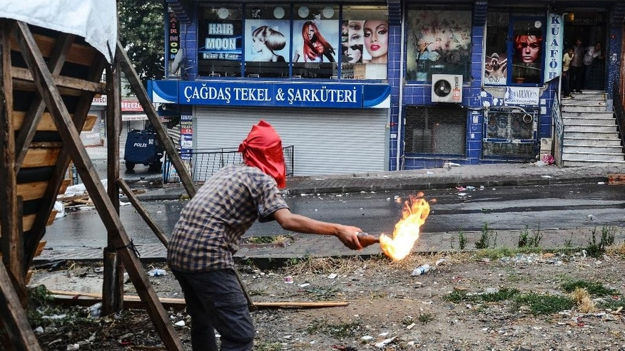 A protester hurls a petrol bomb towards a police car in Istanbul, Friday, July 24, 2015, during clashes between police and protesters denouncing the deaths of 32 people at an suicide bombing Monday in Suruc, southeastern Turkey.  Turkish warplanes struck Islamic State group targets across the border in Syria early Friday, in a strong tactical shift for Turkey which had long been reluctant to join the U.S.-led coalition against the extremist group.  (AP Photo/Cagdas Erdogan, Depo Photos) TURKEY OUT