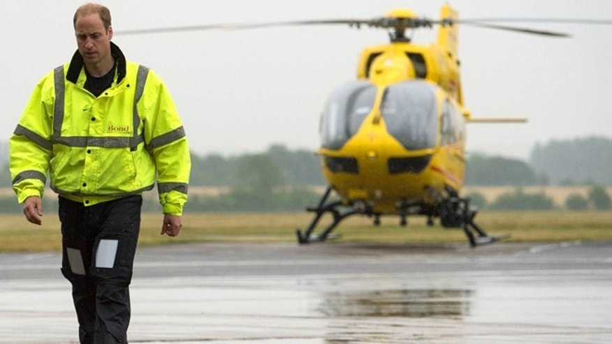 July 13, 2015. Britain's Prince William, the Duke of Cambridge walks, with an East Anglian Air Ambulance (EAAA) in the background, as he begins his new role, at Cambridge Airport, Cambridge, in England.