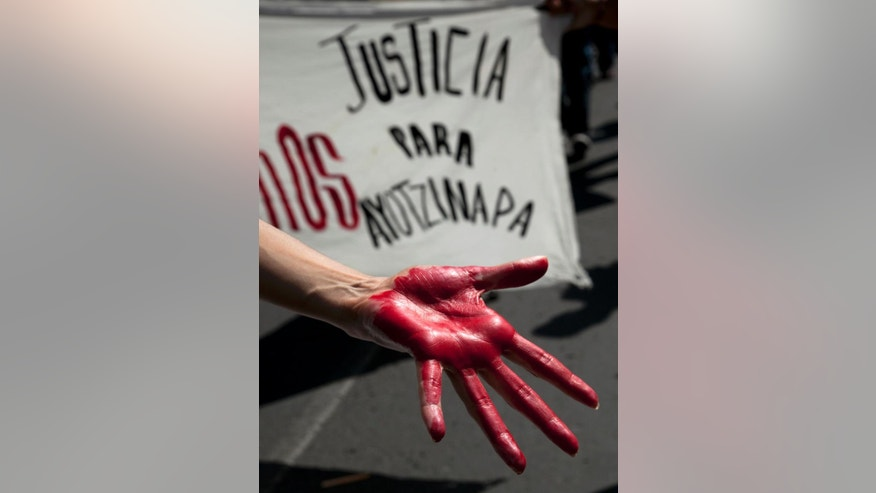 "A woman shows a hand painted red in front of a banner that says: ""Justice for Ayotzinapa"" during a march of relatives of the 43 missing students from the Isidro Burgos rural teachers college in Mexico City, Sunday, July 26, 2015.The search for 43 missing college students in the southern state of Guerrero has turned up at least 60 clandestine graves and 129 bodies over the last 10 months, Mexico's attorney general's office says. None of the remains has been connected to the youths who disappeared after a clash with police in the city of Iguala on Sept. 26, and authorities do not believe any will be.  (AP Photo/Marco Ugarte)"