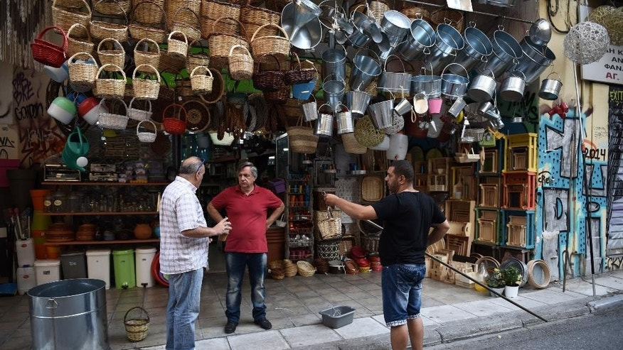 People chat outside a shop in Athens, Saturday, July 25, 2015. Greece on Friday invited the International Monetary Fund to participate in its negotiations with European creditors over a vital third bailout. The talks are expected to start next week after a few days' delay and must conclude before Greece faces another big repayment Aug. 20. (AP Photo/Giannis Papanikos)