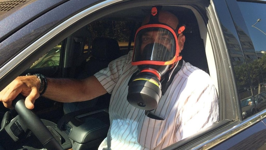 Ziad Jaroudi a Lebanese doctor wears a gas mask to protect against the smell from piles of garbage in the streets, as he drives his car in Beirut, Lebanon, Saturday, July 25, 2015. The Lebanese cabinet has failed to agree on a solution for the country's growing garbage crisis, postponing discussion until next week as trash piles up on the streets. (AP Photo/Hussein Malla)