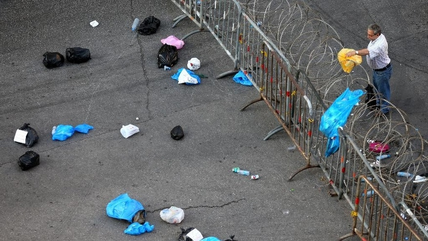 A Lebanese protester, right, throws a trash bag over the barbered wire that blocks a road linked to the government house, as other trash bags are seen on the ground thrown by other protesters, during a demonstration against the the ongoing trash crisis, in downtown Beirut, Lebanon, Saturday, July 25, 2015. The Lebanese cabinet has failed to agree on a solution for the country's growing garbage crisis, postponing discussion until next week as trash piles up on the streets. (AP Photo/Hussein Malla)
