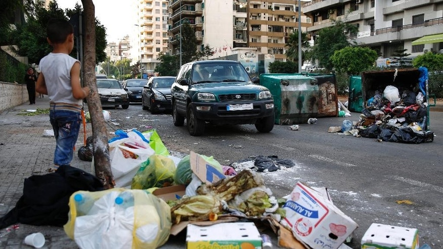 A Syrian boy watches vehicles driving past dumpsters and a pile of garbage in Beirut, Lebanon, Sunday, July 26, 2015. Protesters have closed the highway linking Beirut with southern Lebanon over the country's trash crisis. The closure of the vital highway in the coastal town of Jiyeh on Sunday comes amid reports that the government plans to move trash piled on the streets of Beirut to the Kharoub region south of the capital. (AP Photo/Hassan Ammar)