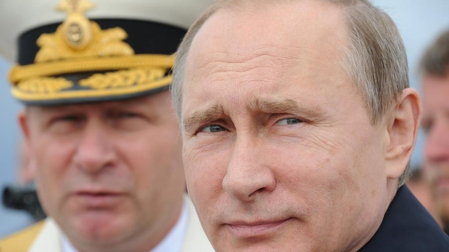Russian President Vladimir Putin, foreground, reviews a Navy parade in Baltisk, western Russia,  Sunday, July  26, 2015, during celebrations  for Russian Navy Day. (Mikhail Klimentyev/RIA-Novosti, Kremlin Pool Photo via AP)