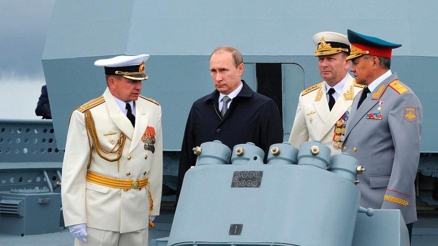 Russian President Vladimir Putin, second left, and Defense Minister Sergei Shoigu, right, with a group of Russian naval officers during a Navy parade in Baltiisk, western Russia, Sunday, July  26, 2015 during celebrations for Russian Navy Day. (Mikhail Klimentyev/RIA-Novosti, Kremlin Pool Photo via AP)