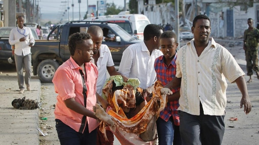Somalis carry away the body of a person who was killed in a suicide car bomb attack in the capital Mogadishu, Somalia Sunday, July 26, 2015. Somali police officer says a suicide car bomber has rammed his car into the protective perimeter outside a well-known hotel in the Somali capital Sunday, killing at least four people. Capt. Mohamed Hussein says the blast has caused an extensive damage on the Jazeera Hotel, which is often frequented by government officials, diplomats and foreigners.  (AP Photo/Farah Abdi Warsameh)