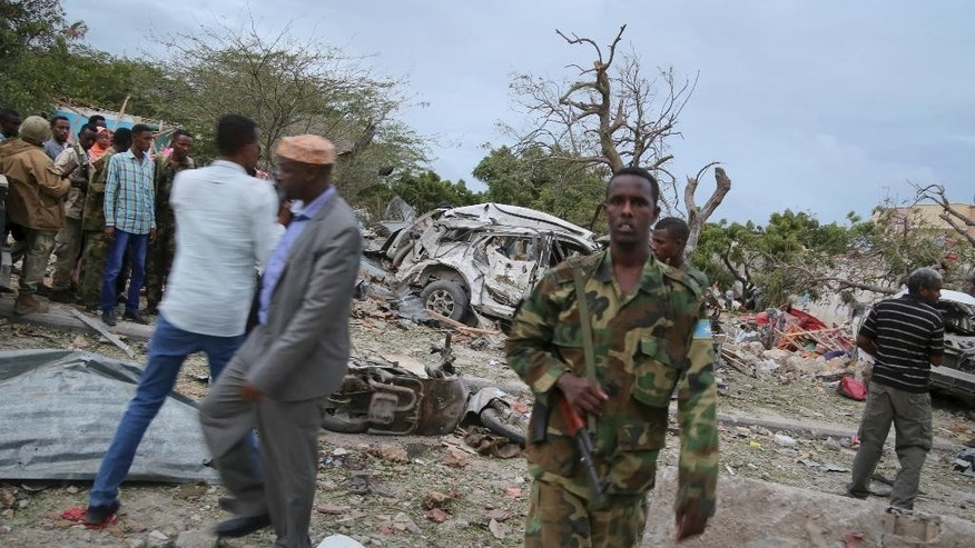 Security forces secure the scene of a suicide car bomb attack in the capital Mogadishu, Somalia Sunday, July 26, 2015. Somali police officer says a suicide car bomber has rammed his car into the protective perimeter outside a well-known hotel in the Somali capital Sunday, killing at least four people. Capt. Mohamed Hussein says the blast has caused an extensive damage on the Jazeera Hotel, which is often frequented by government officials, diplomats and foreigners. (AP Photo/Mohamed Sheikh Nor)
