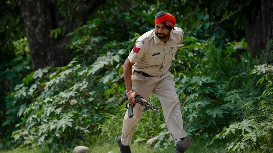 An Indian policeman takes position during a fight in the town of Dinanagar, in the northern state of Punjab, India, Monday, July 27, 2015. Indian army commandos joined police in fighting suspected militants who fired at a bus station and stormed into police barracks on the outskirts of a northern town bordering Pakistan early Monday. Rebels have been fighting for an independent Kashmir or its merger with Pakistan since 1989. (AP Photo/ Channi Anand)