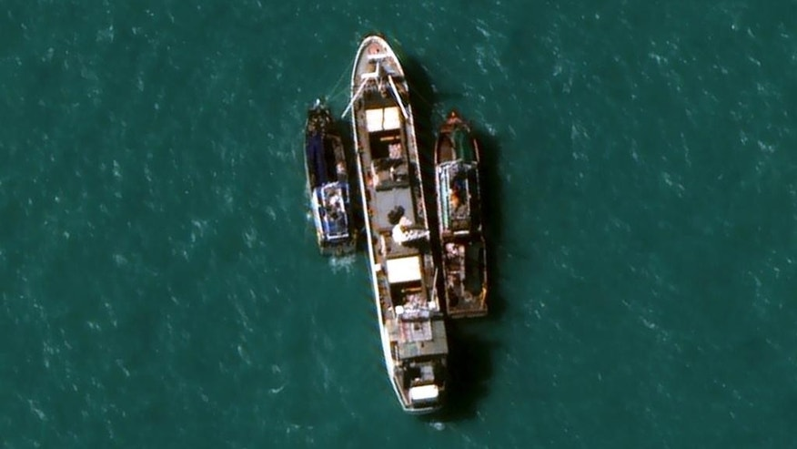 In this July 14, 2015, image provided by DigitalGlobe, a high-resolution satellite photograph off the coast of  Papua New Guinea shows two fishing trawlers loading slave-caught fish onto Silver Sea 2, a refrigerated cargo ship belonging to the Thai-owned Silver Sea Fishery Co. The company was named in an Associated Press investigation into slavery in Southeast Asia's seafood industry that led to the rescue and repatriation of more than 800 men. Hundreds more remain missing after their trawlers fled an Indonesian crackdown on illegal fishing. (DigitalGlobe via AP)