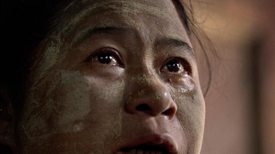 "In this July 16, 2015, photo, Ohn Myint, mother of 19-year-old Myo Ko Ko, a Burmese slave believed to be trapped on a fishing trawler in a narrow strait off Papua New Guinea, weeps in Yangon, Myanmar. ""I miss my son so much, each and every hour,"" she said. ""All I can do is pray for him."" Hundreds of forced laborers remain missing after their boats fled a slave island in Indonesia during a crackdown on illegal fishing. (AP Photo/Gemunu Amarasinghe)"