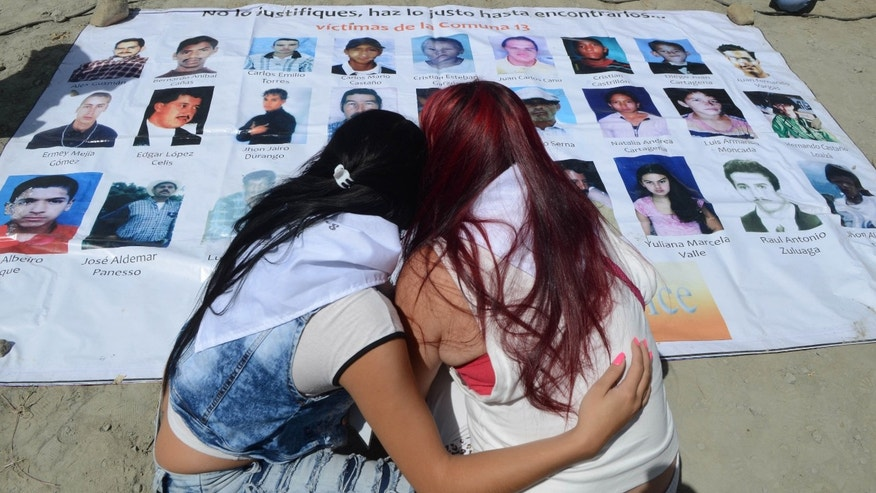 Women look at a poster with images of missing people, during a ceremony to remember the disappeared and kick off a search effort in La Escombrera, on the outskirts of Medellin, Colombia, Monday, July 27, 2015. La Escombrera is a debris landfill where the remains of as many as 300 people are believed to have been dumped during one of the darkest chapters of Colombiaâs long-running civil conflict. Human rights activists say the landfill could prove to be the largest mass grave ever found in Colombia and the dig represents a glimmer of hope that justice will be realized. (AP Photo/Luis Benavides)