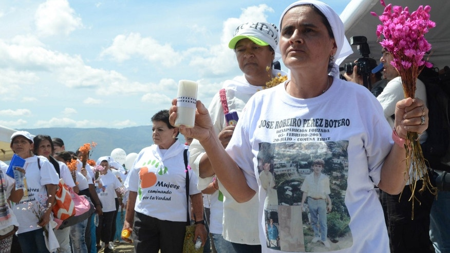 Blanca Nidia Perez, wearing a T-shirt with an image of her disappeared brother, attends a ceremony to remember the missing and kick off a search effort in La Escombrera, on the outskirts of Medellin, Colombia, Monday, July 27, 2015. La Escombrera is a debris landfill on where the remains of as many as 300 people are believed to have been dumped during one of the darkest chapters of Colombiaâs long-running civil conflict. Human rights activists say La Escombrera could prove to be the largest mass grave ever found in Colombia and the dig represents a glimmer of hope that justice will be realized. (AP Photo/Luis Benavides)