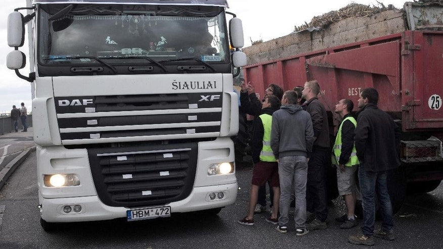 French farmers control trucks at the French-German border on the Rhine bridge in Strasbourg, eastern France, in order to stop importation of foreign meat and milk products in France, Monday, July 27, 2015. French farmers angry over low prices are massed on the German and Spanish borders, looking for trucks carrying foreign meat and milk products. The government last week offered a 600 million euro ($654 million) agricultural plan to back loans and delay tax payments for farmers, but they say it is not enough.  (AP Photo/Christian Lutz)