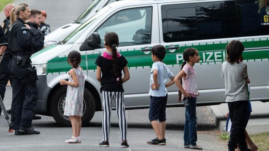 FILE - In this June 26, 2015 file photo Refugee children stand in front of a police car near the accommodation for immigrants in Freital near Dresden, eastern Germany. The head of the German Police Union is calling for a ban on demonstrations within a kilometer of centers housing refugees amid a string of violent incidents. Germany is seeing a rise in anti-foreigner attacks and vandalism amid a spike in asylum applications, which are expected to double this year. (AP Photo/Jens Meyer)
