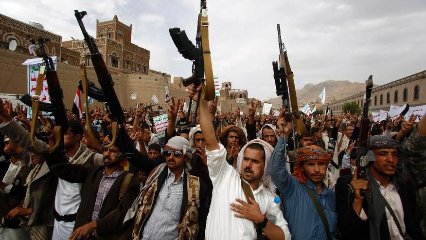 FILE - In this Friday, July 24, 2015, file photo, Shiite rebels known as Houthis hold up their weapons as they chant slogans during a rally against Saudi-led airstrikes in Sanaa, Yemen. (AP Photo/Hani Mohammed, File)