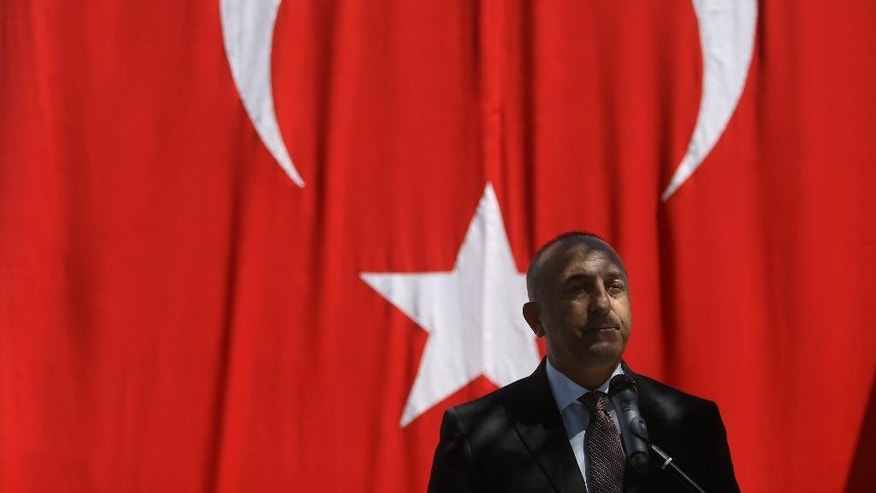 Turkish Foreign Minister Mevlut Cavusoglu delivers a speech during a ceremony in honour of the Portuguese policeman and a Turkish citizen who were victims of an attack on the Turkish embassy in Lisbon by an Armenian group in 1983, in Lisbon, Monday, July 27, 2015.  (AP Photo/Francisco Seco)