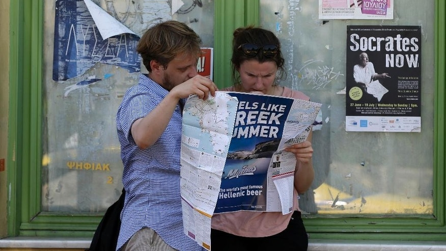 Tourists read a map in Athens, Monday, July 27, 2015. The government has already begun imposing new austerity measures demanded in return for the new bailout — but had relied on support from opposition parties after nearly a quarter of lawmakers in the ruling Syriza party opposed him. (AP Photo/Thanassis Stavrakis)