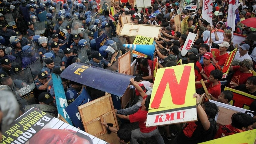 "Protesters clash with police as they try to force their way closer to the House of Representatives to coincide with the last State-of-the-Nation-Address or SONA of Philippine President Benigno Aquino III at suburban Quezon city northeast of Manila, Philippines Monday, July 27, 2015. The protesters assailed the Aquino administration for its alleged failures to address the ""lingering problems"" of the people. (AP Photo/Bullit Marquez)"