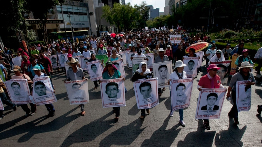 Relatives of the 43 missing students from the Isidro Burgos rural teachers college march holding pictures of their missing loved ones during a protest in Mexico City, Sunday, July 26, 2015.The search for 43 missing college students in the southern state of Guerrero has turned up at least 60 clandestine graves and 129 bodies over the last 10 months, Mexico's attorney general's office says. None of the remains has been connected to the youths who disappeared after a clash with police in the city of Iguala on Sept. 26, and authorities do not believe any will be.  (AP Photo/Marco Ugarte)