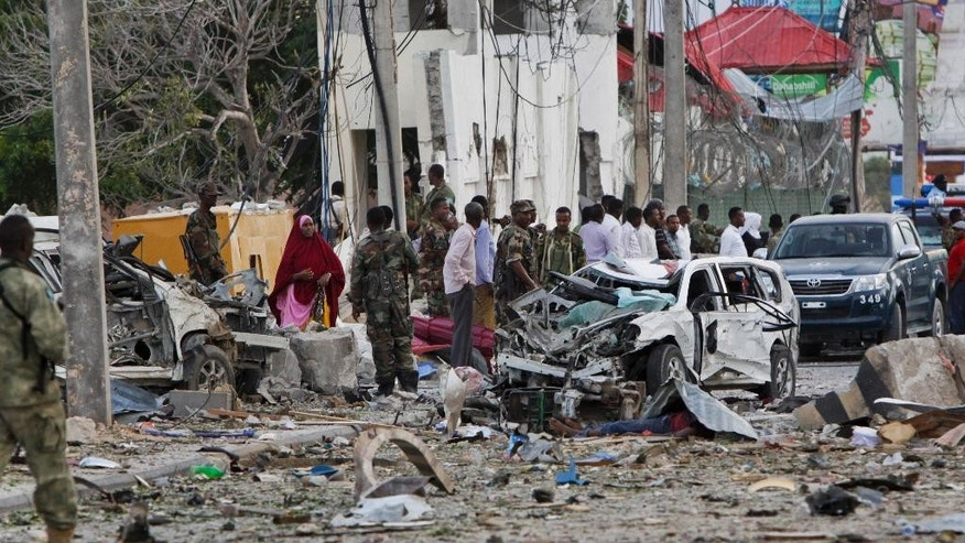 Security forces secure the scene next to destroyed vehicles following a suicide car bomb attack in the capital Mogadishu, Somalia Sunday, July 26, 2015. A Somali police officer says a suicide car bomber has rammed his car into the protective perimeter outside a well-known hotel in the Somali capital Sunday, killing at least four people. Capt. Mohamed Hussein says the blast has caused an extensive damage on the Jazeera Hotel, which is often frequented by government officials, diplomats and foreigners. (AP Photo/Farah Abdi Warsameh)