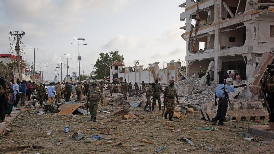 Security forces secure the scene following a suicide car bomb attack in the capital Mogadishu, Somalia Sunday, July 26, 2015. A Somali police officer says a suicide car bomber has rammed his car into the protective perimeter outside a well-known hotel in the Somali capital Sunday, killing at least four people. Capt. Mohamed Hussein says the blast has caused an extensive damage on the Jazeera Hotel, which is often frequented by government officials, diplomats and foreigners. (AP Photo/Farah Abdi Warsameh)