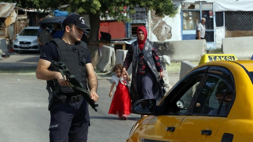 A police officer checks IDs as Turkish police raid homes in the Haci Bayram neighborhood of the capital Ankara, Turkey, Monday, July 27, 2015. Security forces has detained at least 15 people suspected of links to the Islamic State group, the state-run news agency said. The Anadolu Agency said those detained in the Haci Bayram neighborhood include a number of foreign nationals. It did not give details of the foreigners' home countries. (AP Photo/Burhan Ozbilici)