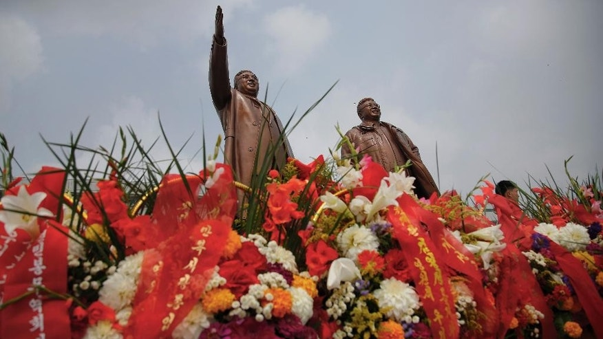 Bronze statues of the late leaders Kim Il Sung, left, and Kim Jong Il tower over flower offerings at Munsu Hill, Monday, July 27, 2015, in Pyongyang, North Korea. North Koreans gathered to offer flowers and pay their respects to their late leaders as part of celebrations for the 62nd anniversary of the armistice that ended the Korean War. (AP Photo/Wong Maye-E)