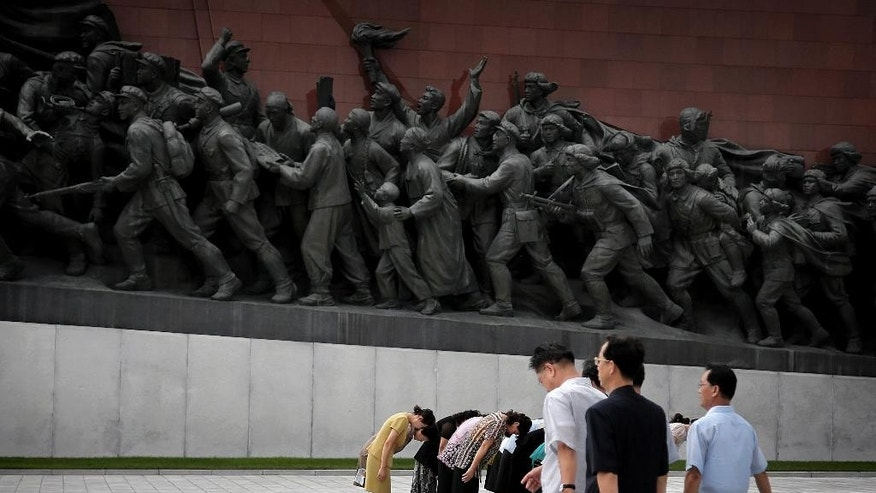 North Koreans bow to bronze statues of the late leaders Kim Il Sung and Kim Jong Il at Munsu Hill, Monday, July 27, 2015, in Pyongyang, North Korea. North Koreans gathered to offer flowers and pay their respects to their late leaders as part of celebrations for the 62nd anniversary of the armistice that ended the Korean War. (AP Photo/Wong Maye-E)