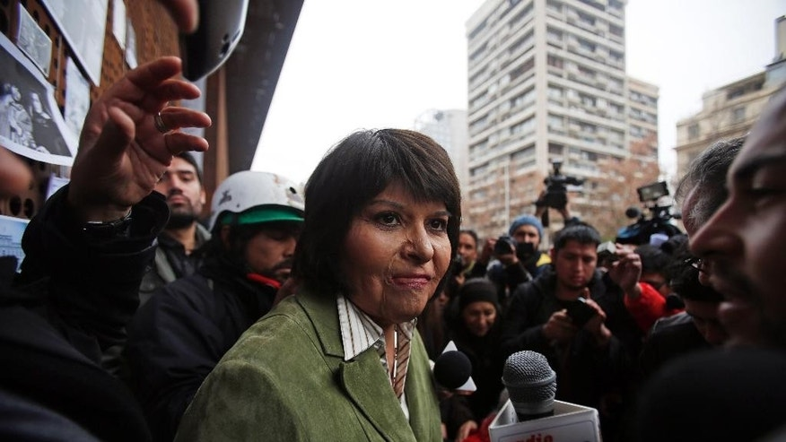 Carmen Quintana attends a tribute for slain photographer Rodrigo Rojas, outside the Gabriela Mistral museum, in Santiago, Chile, Tuesday, July 28, 2015. During a street demonstration on July 2, 1986, soldiers doused Rojas and then 18-year-old Quintana with gasoline and set them ablaze. Rojas died four days later. Quintana survived and underwent lengthy treatment for severe burns at a Canadian hospital. Her scarred face later became a symbol of the atrocities committed by Pinochet's dictatorship. A Chilean judge last week charged seven former members of the military in the burning death of Rojas, and four other ex-soldiers were being questioned on Monday. (AP Photo/Luis Hidalgo)