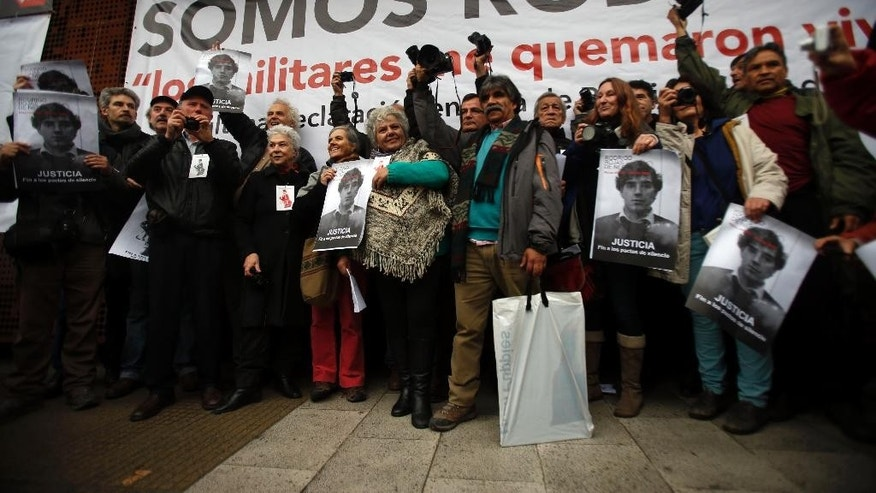 Veronica de Negri, center, holds a poster with the image of her slain photographer son Rodrigo Rojas, during a tribute to her son, outside the Gabriela Mistral museum, in Santiago, Chile, Tuesday, July 28, 2015. During a street demonstration on July 2, 1986, soldiers doused Rojas and 18-year-old Carmen Quintana with gasoline and set them ablaze. Rojas died four days later. A Chilean judge last week charged seven former members of the military in the burning death of Rojas, and four other ex-soldiers were being questioned on Monday. The charges come after another soldier testified about the case last year, breaking a nearly three-decade pact of silence. (AP Photo/Luis Hidalgo)