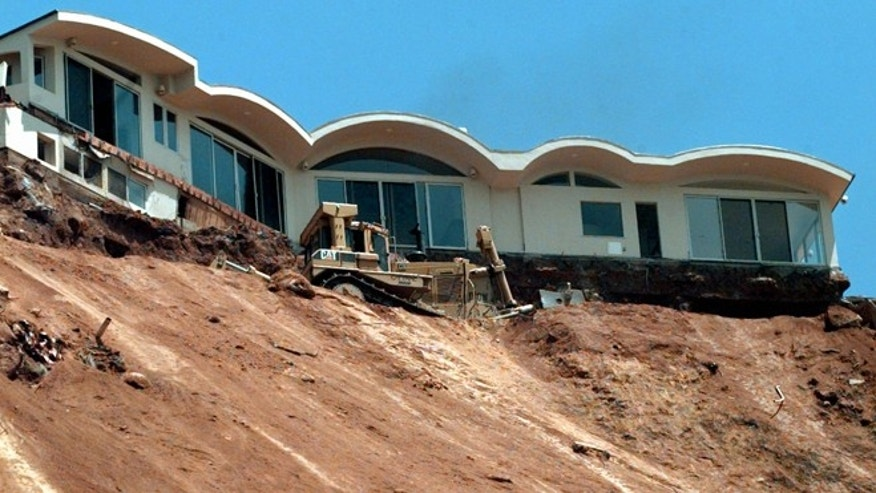 FILE - In this June 25, 1998 file photo, a Caltrans bulldozer terraces a sliding hillside below the condemned home above Pacific Coast Highway near Las Flores Canyon Road in Malibu, Calif. The home and at least one other at the top of the slide was scheduled for demolition. It can be both godsend and catastrophe. In California, they're counting on it to end a more than $2 billion drought and in Peru they have already declared a pre-emptive emergency, reinforcing protection against devastating flooding. It's both an economic stimulus and a recession-maker. And it's likely to increase the price of coffee, chocolate and sugar.  (AP Photo/Reed Saxon, File)