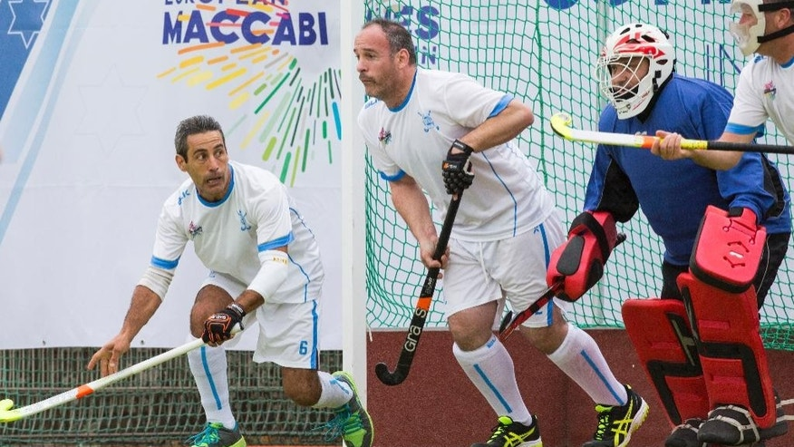 From left, Israel's Arman Vanaian, Larry Sherman, Greg Meyers and Victor Hugo Carmona try to block the ball during the Open men  hockey match between Israel and Germany at the European Maccabi Games in Berlin, Germany, Tuesday, July 28, 2015. More than 2,000 Jewish athletes are gathering in Berlin for the European Maccabi Games, being held for the first time in Germany, and  at sites constructed by the Nazis for the 1936 Olympics. (AP Photo/Gero Breloer)