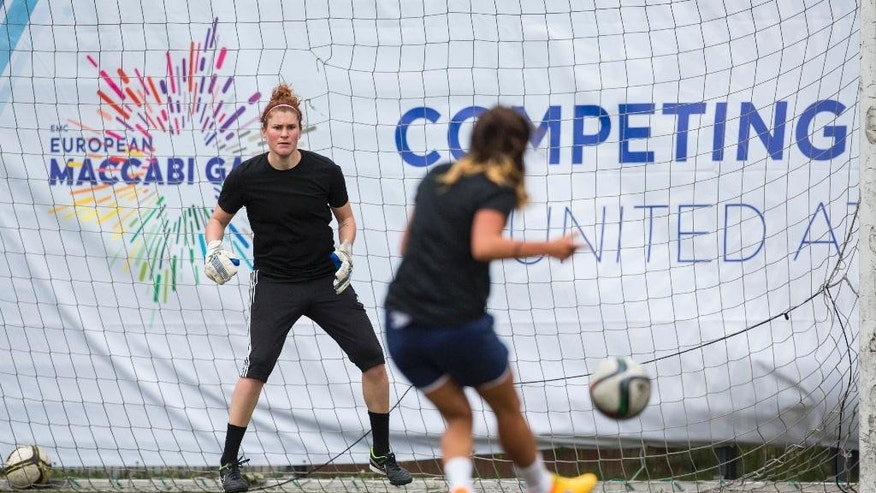 Goalkeeper Merav Shamir, left, of the German Open Female national soccer team waits for a shot of her   Lee Falkon during a training session at the European Maccabi Games in Berlin, Germany, Tuesday, July 28, 2015. More than 2,000 Jewish athletes are gathering in Berlin for the European Maccabi Games, being held for the first time in Germany, and  at sites constructed by the Nazis for the 1936 Olympics. (AP Photo/Gero Breloer)